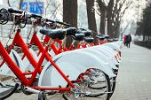 Public Bike Rental Station In Beijing, China With Bicycles Arranging In Row Ready For Public Rental poster