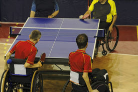 picture of ping pong  - Image of a disabled persons in wheelchairs playing a double table tennis game - JPG