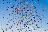 stock photo of mardi-gras  - Confetti paper filled colorful blue sky background - JPG
