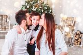 Christmas Family Smiling And Kissing Near The Xmas Tree. Living Room Decorated By Christmas Tree And poster