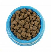 Blue Round Feeding Bowl With Dark Brown Heart Shaped Dog Or Cat Kibble Seen From Above Isolated On A poster