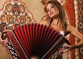 Sexy lady playing accordion over an asian carpet background