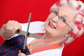 pic of serial killer  - grandmother with haircurlers sharpening knives against red background - JPG