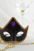 Black carnival mask with glass martini in background isolated on a white background