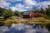 An Abandoned Red Sinking Barn Sinks Into A Lake Near Zimmerman, Minnesota poster