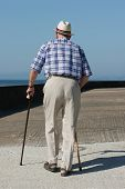 Rear view of an elderly man walking with walking sticks on a beach promenade.