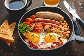 Full English breakfast - fried egg, baked beans, bacon, sausages on a dark rusty background, toasts, poster