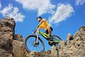 Person riding a mountain bike amid rocks on a sunny day against a blue sky and clouds, low angle vie