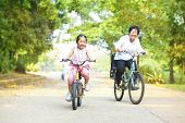 Little Asian girl and grandmother riding on bicycle with great fun