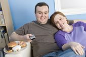 Obese couple watching television at home