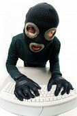 stock photo of shoplifting  - Image of criminal in balaclava pressing buttons of keyboard - JPG