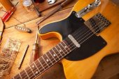 Guitar on guitar repair desk. Vintage electric guitar on a guitar repair work shop. Single cutaway s