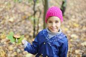 stock photo of face-fungus  - Happy girl in pink hat holds green leaf and toadstool in autumn forest - JPG