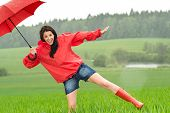 Playful happy girl in the rain with red umbrella