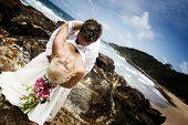 foto of wedding couple  - Passionate young couple getting married on the beach standing on rocks - JPG