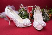 stock photo of wench  - white weddin shoes on a red background - JPG