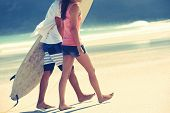 foto of watersports  - Hispanic couple walk on beach together with surfboard having fun outdoors - JPG