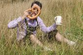 image of lederhosen  - Young man in traditional Bavarian lederhosen relaxing in the field - JPG