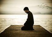 stock photo of muslim man  - Muslim man fasting Ramadan and praying on beautiful lake  - JPG
