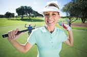 stock photo of ladies golf  - Lady golfer smiling at camera with partner cheering behind on a sunny day at the golf course - JPG