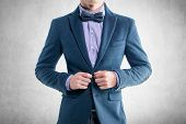 stock photo of single man  - Handsome elegant young fashion man in coat tuxedo classical suit and bow tie - JPG