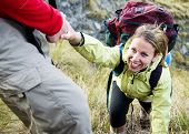 stock photo of helping others  - Hikers helping each other up a mountain - JPG