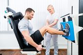 pic of physical therapist  - Patient at the physiotherapy doing physical exercises using leg press in sport remobilization - JPG