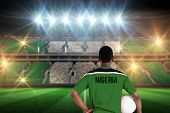 picture of nigeria  - Nigeria football player holding ball against stadium full of nigeria football fans - JPG