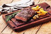 stock photo of ribeye steak  - Sliced medium rare grilled Beef steak Ribeye with roasted potato wedges on cutting board on wooden background - JPG