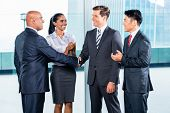 stock photo of contract  - Diversity business team concluding contract with handshake in front of city skyline - JPG