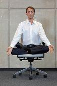 stock photo of pranayama  - meditating caucasian businessman in lotus pose on office chair - JPG