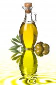 stock photo of kalamata olives  - Bottle of extra virgin olive oil and olives with leaves on liquid reflections - JPG