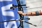 stock photo of bow arrow  - Bow and arrow in the hands of an archer - JPG