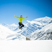image of mountain-climber  - Happy young male hiker jumping in white winter mountains Himalayas - JPG