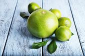 picture of sweetie  - Ripe sweetie and limes on wooden background - JPG