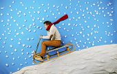 stock photo of toboggan  - Happy young man on sled having fun against the blue background with snowflakes - JPG
