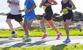 image of competing  - Group of runners compete in the race on coastal road - JPG