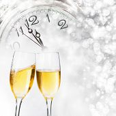 picture of midnight  - Glasses with champagne against holiday lights and clock close to midnight - JPG