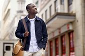 stock photo of urbanization  - Friendly young trendy african black man walking around the urban city having fun - JPG