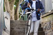 pic of bicycle gear  - Man carrying bicycle down some stairs in city on his way to work - JPG