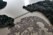 picture of mudslide  - A boom in a dammed river and lake holds back logs from a massive mudslide - JPG