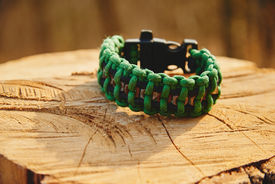 foto of paracord  - Bracelet paracord on a tree trunk in autumn forest no people - JPG