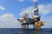foto of rig  - Offshore Jack Up Drilling Rig Over The Production Platform in The Middle of The Sea - JPG