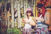 foto of woman  - Closeup of two teenage girls with smart phones. Two young women with hats and shades using smartphones against colorful painted wall outdoors in summer.