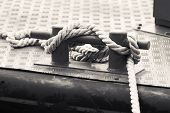 stock photo of bollard  - Black steel bollard with ropes mounted on a ship deck monochrome photo - JPG