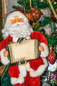 stock photo of accordion  - Christmas santa toy playing the accordion holiday background - JPG