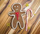 foto of gingerbread man  - holiday classic a gingerbread man with a candy cane cookie on a wooden table - JPG