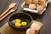 image of egg whites  - Three raw eggs in rustic bowl with egg box with eggs and eggshells in the back photographed on dark wood with natural light  - JPG