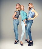 foto of young woman posing the camera  - Three beautiful young woman posing in fashionable jeans looking at camera - JPG