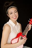 foto of ukulele  - Attractive teen girl model playing ukulele smiling - JPG